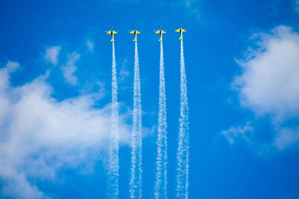 Four planes flying across a blue sky to represent QA processes heading towards business goals