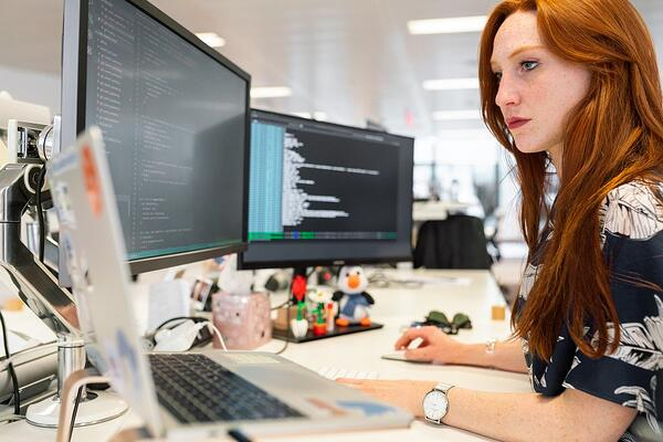 Woman looking at two computer screens doing software testing