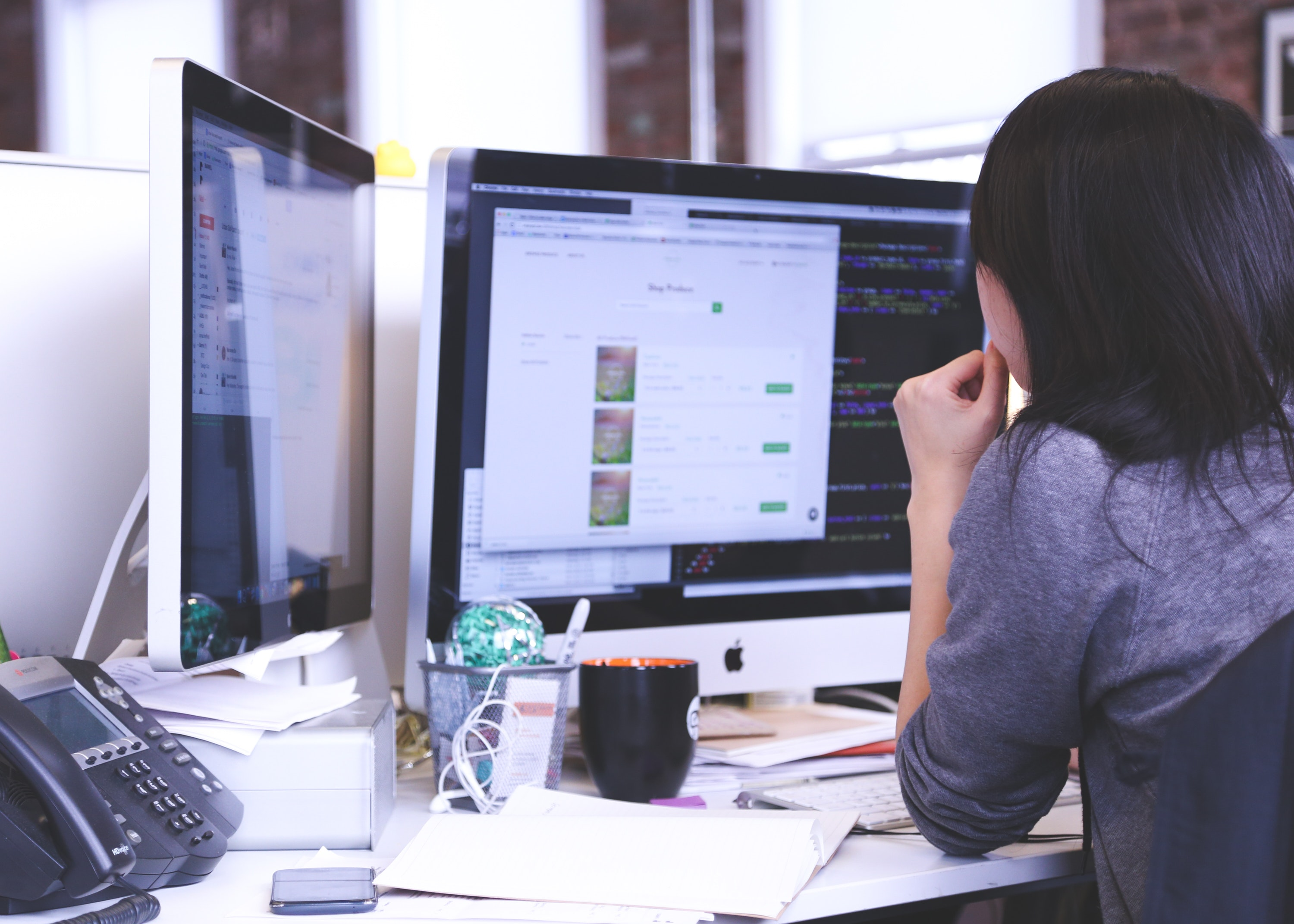 OnPath testing - a woman working at a desk with two monitors